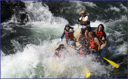 A group of youth going through a class 3 river rapid, grinning and paddling
