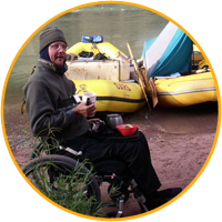 Daniel in his wheelchair next to the rafts on the Colorado River