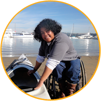 Elena in her wheelchair, preparing to transfer to her sea kayak