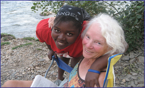 Volunteer Muriel and a Youth LEADer with their arms around each other's shoulders, by the river